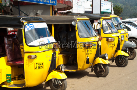 yellow auto rickshaws lined up in