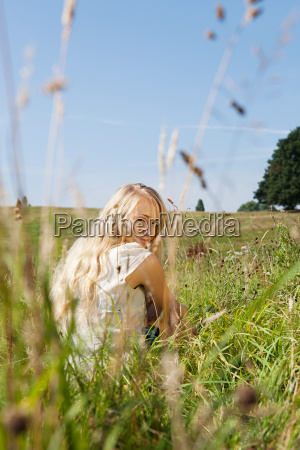 young woman sitting in a field