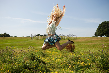 young woman in a field jumping