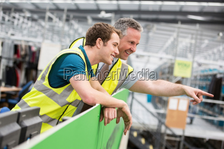two men in warehouse one pointing