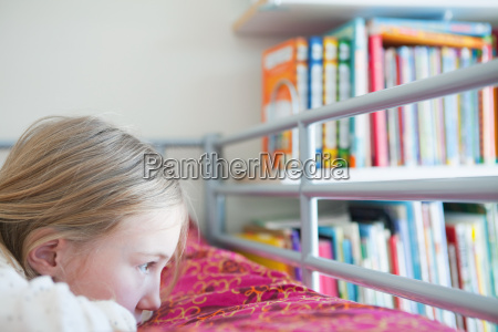 young wistful girl lying on bed