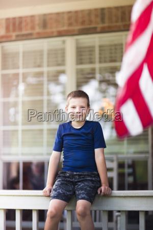 boy sitting on railing