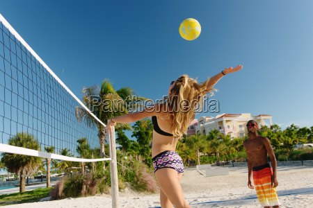 young adult friends playing beach volleyball