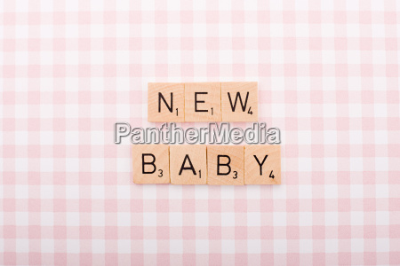 game tile letters spelling new baby