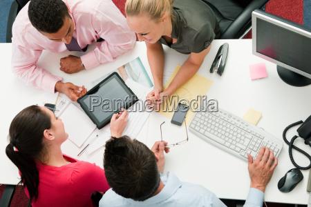 four employees gathered around a digital
