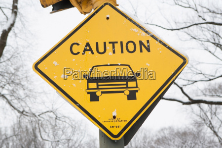 snowy caution road sign