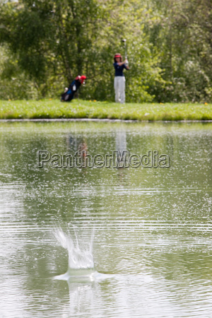 person hitting golf ball into water