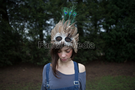 young woman with feathered mask on