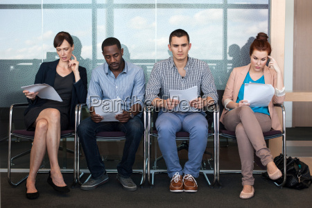 four people sitting on chairs with