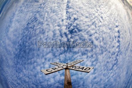 railroad crossing sign under blue sky