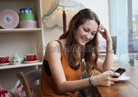 young woman in cafe using cell