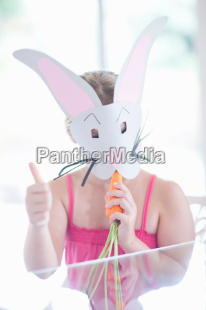 girl in rabbit costume eating carrot