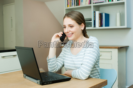 young woman using laptop and phone