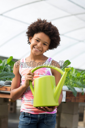 girl holding green watering can