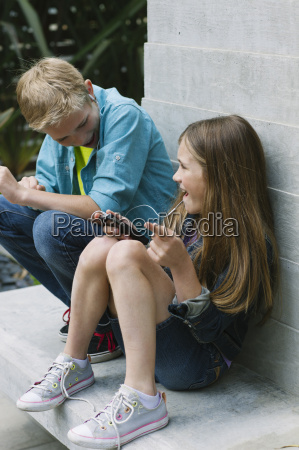 girl and boy laughing girl using