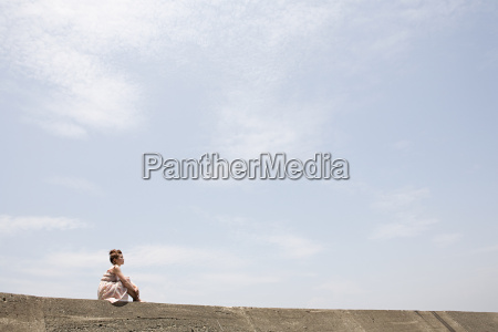 young woman sitting on wall