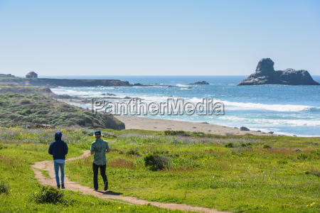 two young male friends walking coastal