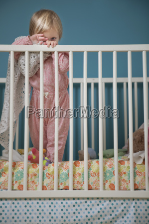 portrait of female toddler hiding behind