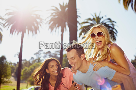 man and women playing piggy back