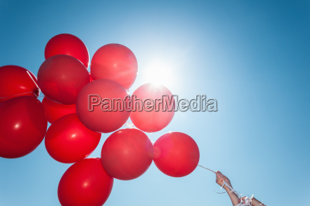 hands holding bunch of red balloons