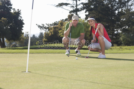 young female golfer taking advice from