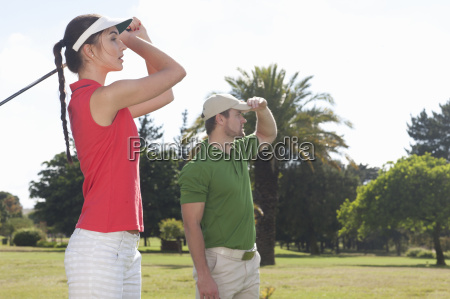 young female practicing golf with trainer