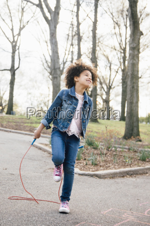 girl standing on one leg playing