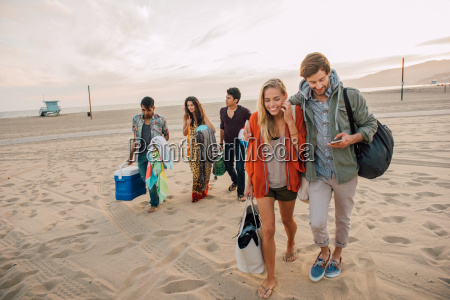 group of friends walking along beach
