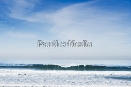 distant view of surfers on ocean