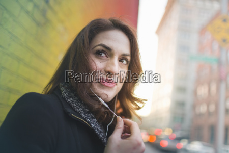 young woman listening to earphones on