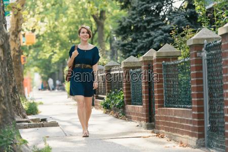 mid adult woman walking down street
