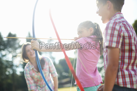 girl learning archery from teenage sister