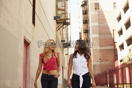women walking and chatting on street