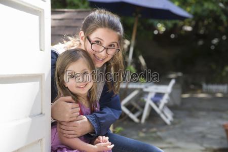 girl hugging sister in garden