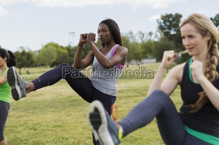 women doing aerobics class in park