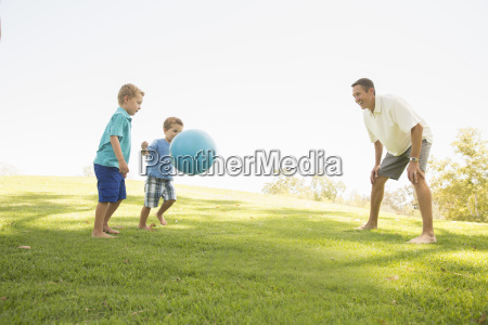 father and sons playing ball at