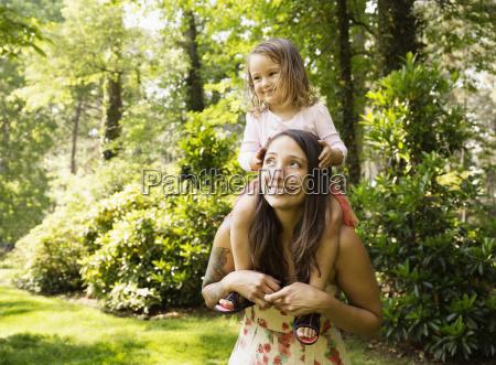 mother giving toddler daughter a shoulder