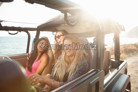 three young women driving in jeep