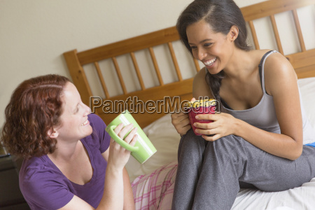 young women sitting on bed holding