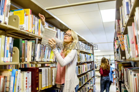 young female librarian searching for books