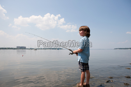 young boy fishing on beach