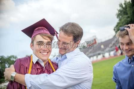 young man being hugged by father