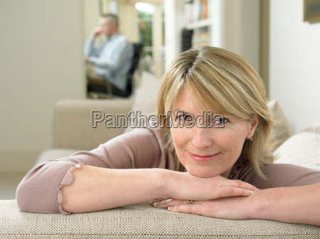 smiling woman resting on sofa