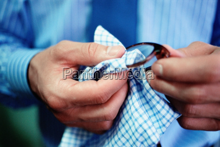 man cleaning spectacle lenses
