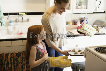 girl and mid adult mother baking