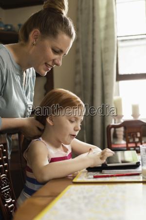 girl using digital tablet at dining