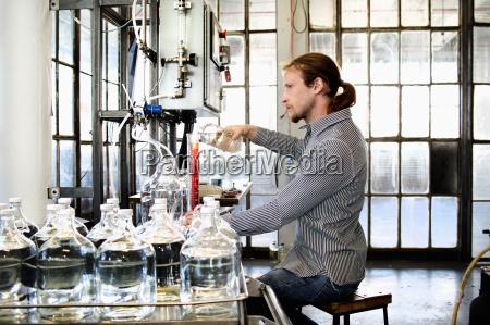 young male vodka distiller pouring liquid