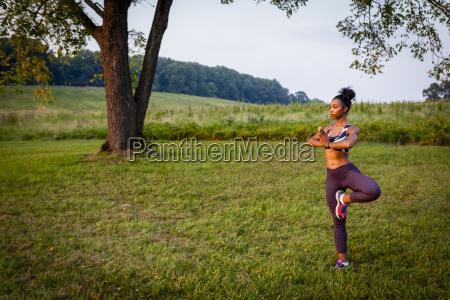 young woman doing yoga tree pose