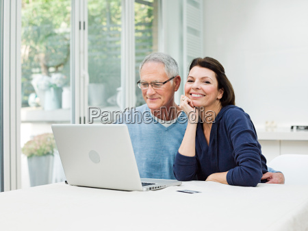 mature couple using laptop with credit