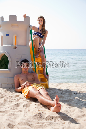 young couple on beach woman sitting